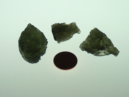 Example of moldavites in our Impact Rock Kits. Note: circular object is U.S.A. penny for scale.